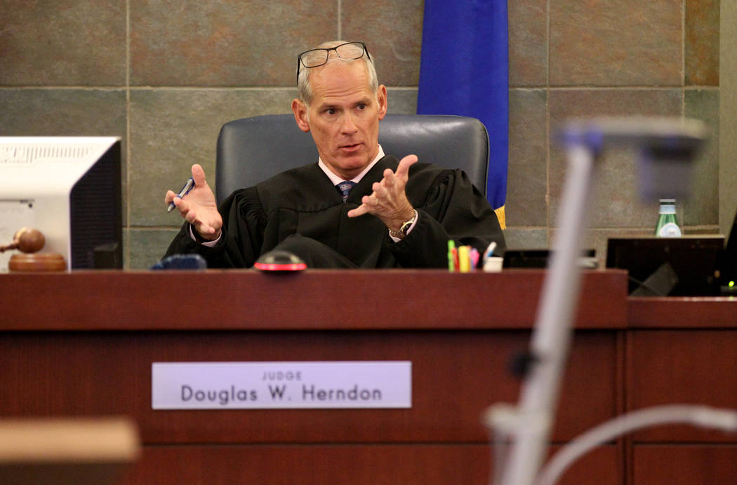 Judge Douglas Herndon talks to attorneys in Clark County District Court in Las Vegas Wednesday, Nov. 7, 2018, before closing arguments in the murder trial of Casey Sandoval, who fatally shot his g ...