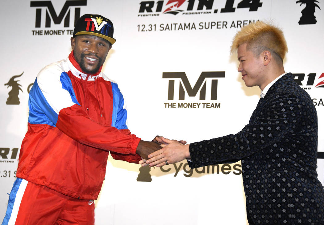 Floyd Mayweather, left, of the U.S. shakes hands with Japanese kickboxer Tenshin Nasukawa during a press conference in Tokyo, Monday, Nov. 5, 2018. Mayweather said he has signed to fight Nasukawa ...