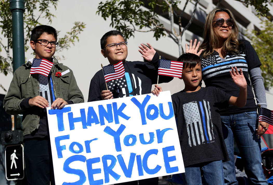 Garrison Munson, 12, from left, his brother Ashton Munson, 13, and his brother Hudson Munson, 7, cheer for the floats with their mother Benjawan Munson at the Veterans Day Parade in Las Vegas, Sun ...