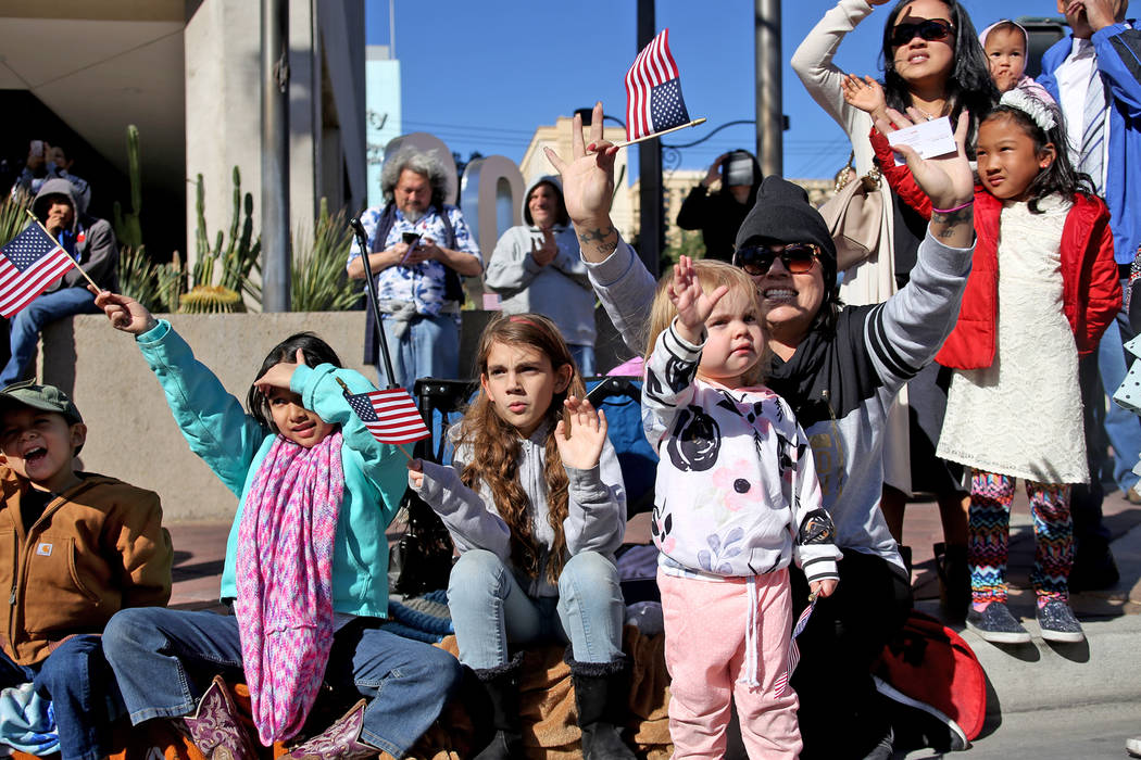 Daniel Rodriguez, 4, from left, his sister Eva Rodriguez, their friends Kaylee Boxford, 9, Alana Boxford, 2, and Liz Boxford cheer for the floats at the Veterans Day Parade in Las Vegas, Sunday, N ...