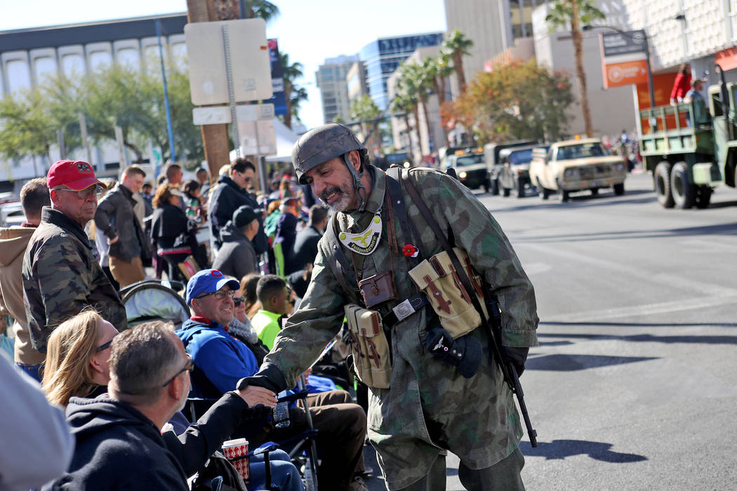 A military police member shakes hands with the crowd during the Veterans Day Parade procession in Las Vegas, Sunday, Nov. 11, 2018. Rachel Aston Las Vegas Review-Journal @rookie__rae