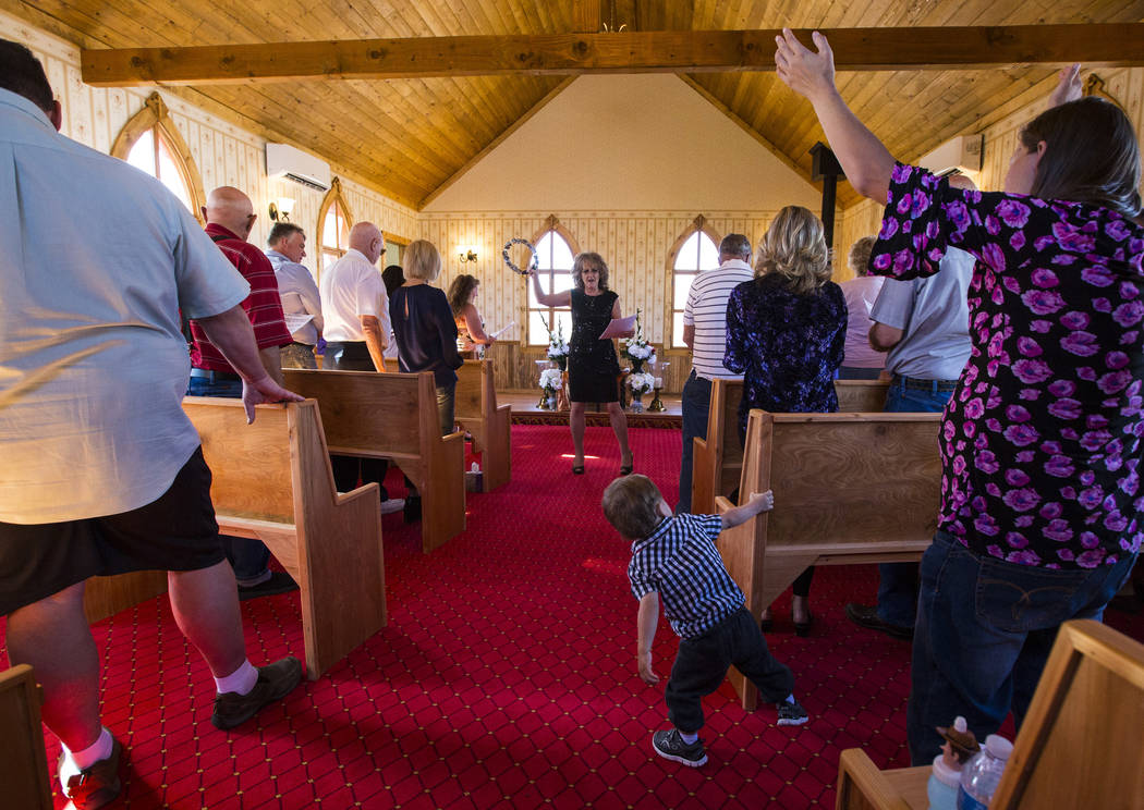 Sherry Donegan of the Church of Amargosa, center, leads a service for the opening of the Chapel at Longstreet, a replica of a Catholic church in Belmont, at Marsh's Longstreet Casino in Amargosa V ...