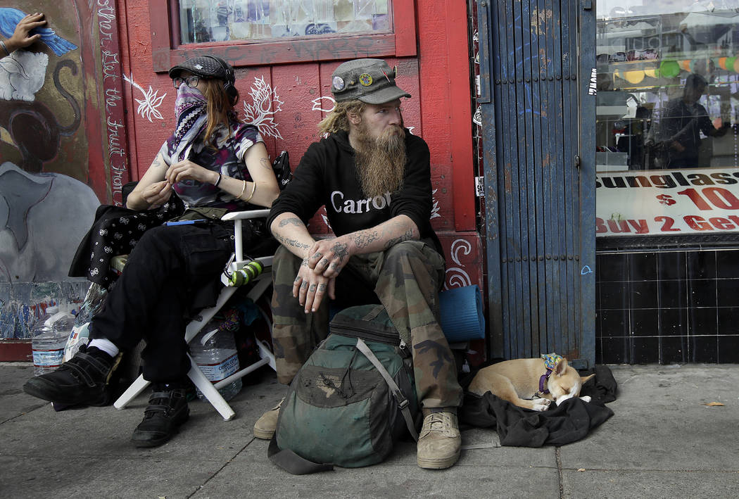 Stormy Nichole Day, left, sits on a sidewalk on Haight Street with Nord (last name not given) and his dog Hobo while interviewed about being homeless in San Francisco on Oct. 1, 2018. (AP Photo/Je ...
