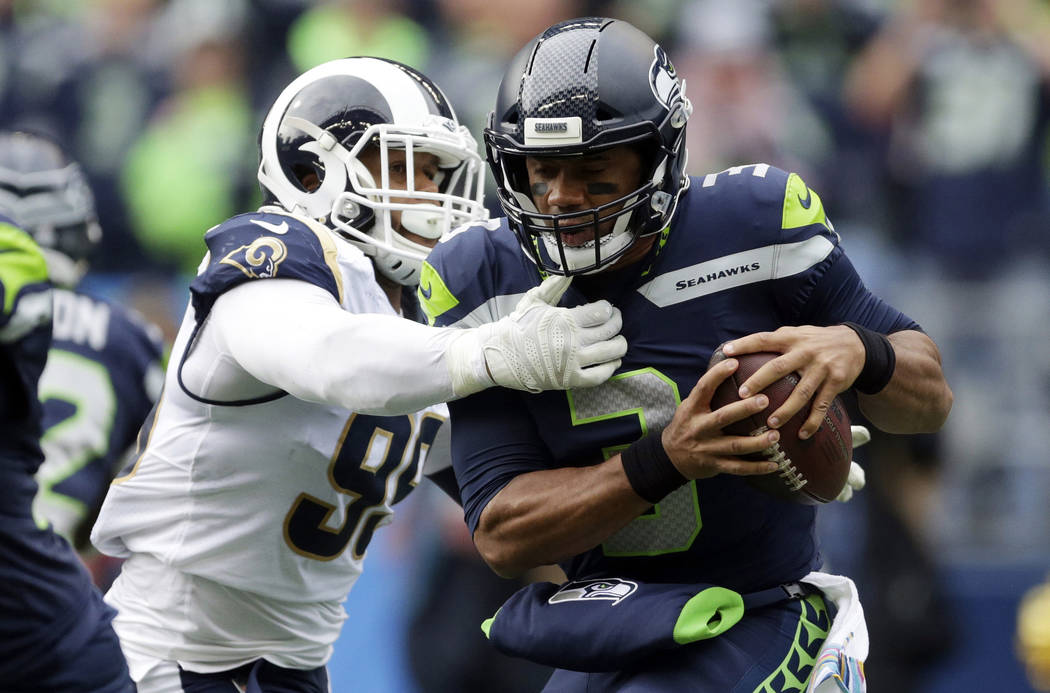 In this Oct. 7, 2018, file photo, Seattle Seahawks quarterback Russell Wilson, right, is sacked by Los Angeles Rams defensive tackle Aaron Donald, left, during the first half of an NFL football ga ...