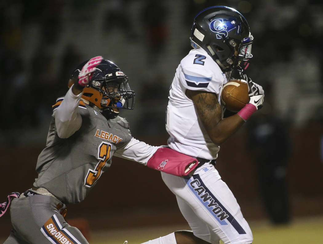 Canyon Springs' Shakureon Dukes (2) pulls in a reception in front of Legacy's Anthony Myles (3) during the first half of a football game at Legacy High School in North Las Vegas on Thursday, Oct. ...