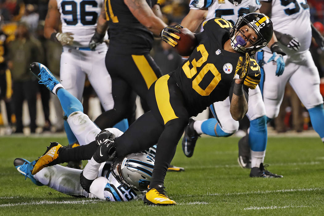 Pittsburgh Steelers running back James Conner (30) is tackled by Carolina Panthers strong safety Eric Reid (25) during the first half of an NFL football game in Pittsburgh, Thursday, Nov. 8, 2018. ...