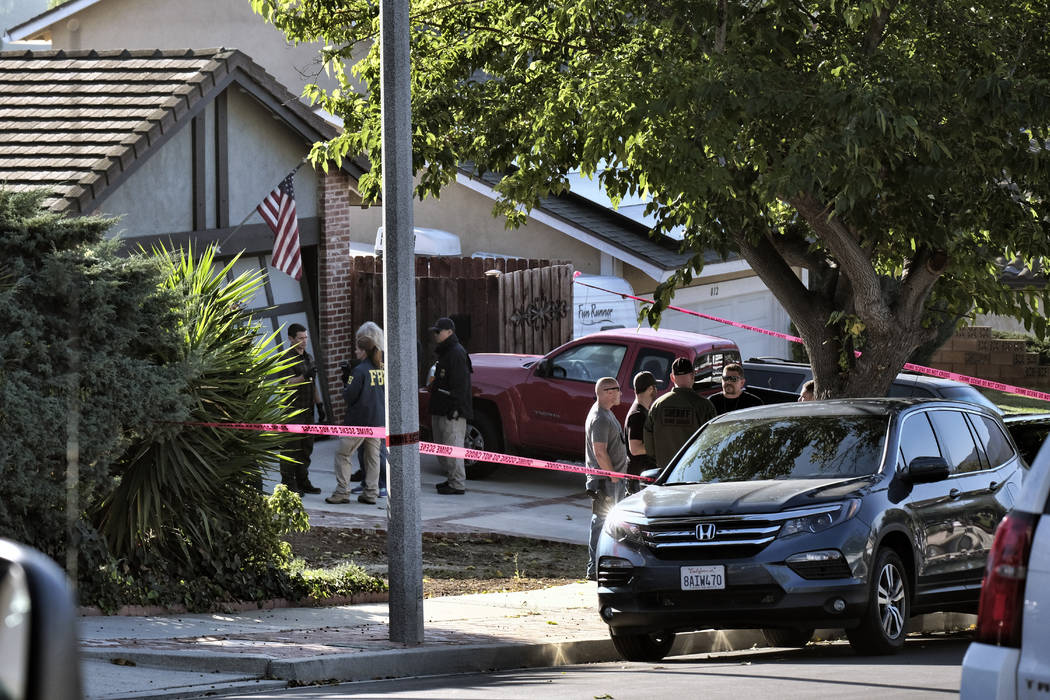 Ventura County Sheriff's deputies and FBI investigators stand outside the house of shooting suspect David Ian Long in Newbury Park, Calif., on Thursday, Nov. 8, 2018. Authorities said the former M ...