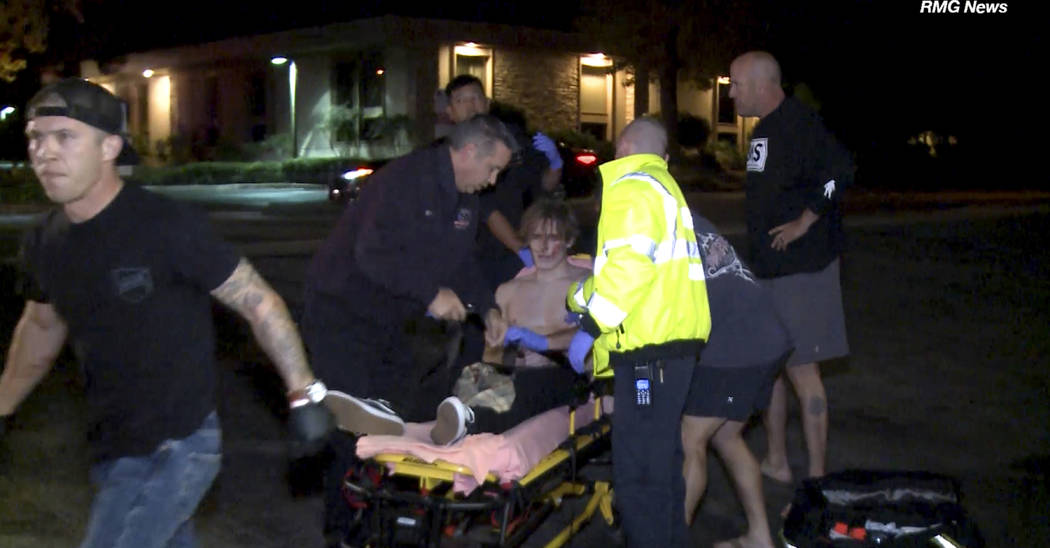 In this image taken from video a victim is treated near the scene of a shooting, Wednesday evening, Nov. 7, 2018, in Thousand Oaks, Calif. A hooded gunman dressed entirely in black opened fire on ...