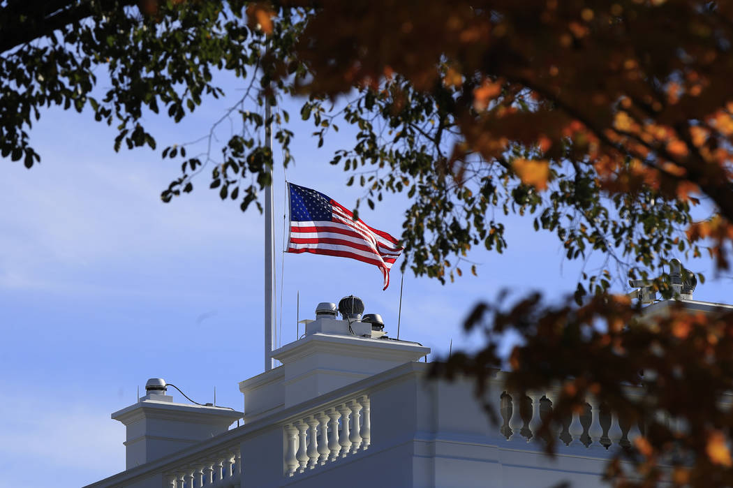 The American flag is lowered at half-staff at the White House in Washington, Thursday, Nov. 8, 2018, to honor the victims of the shooting at a bar in Thousand Oaks, Calif. A hooded former Marine o ...