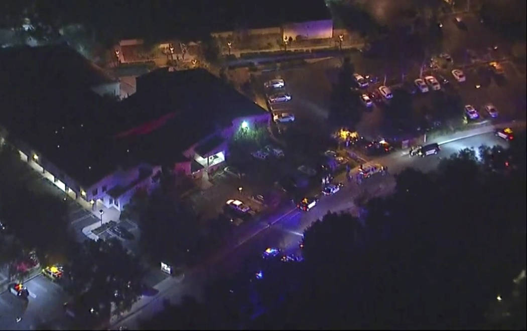 In this image made from aerial video, police vehicles line a road in the vicinity of a shooting in Thousand Oaks, California, early Thursday, Nov. 8, 2018. Authorities say there were multiple inj ...
