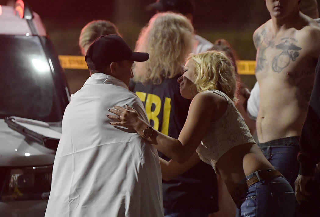 People comfort each other as they stand near the scene Thursday, Nov. 8, 2018, in Thousand Oaks, Calif. where a gunman opened fire Wednesday inside a country dance bar crowded with hundreds of peo ...
