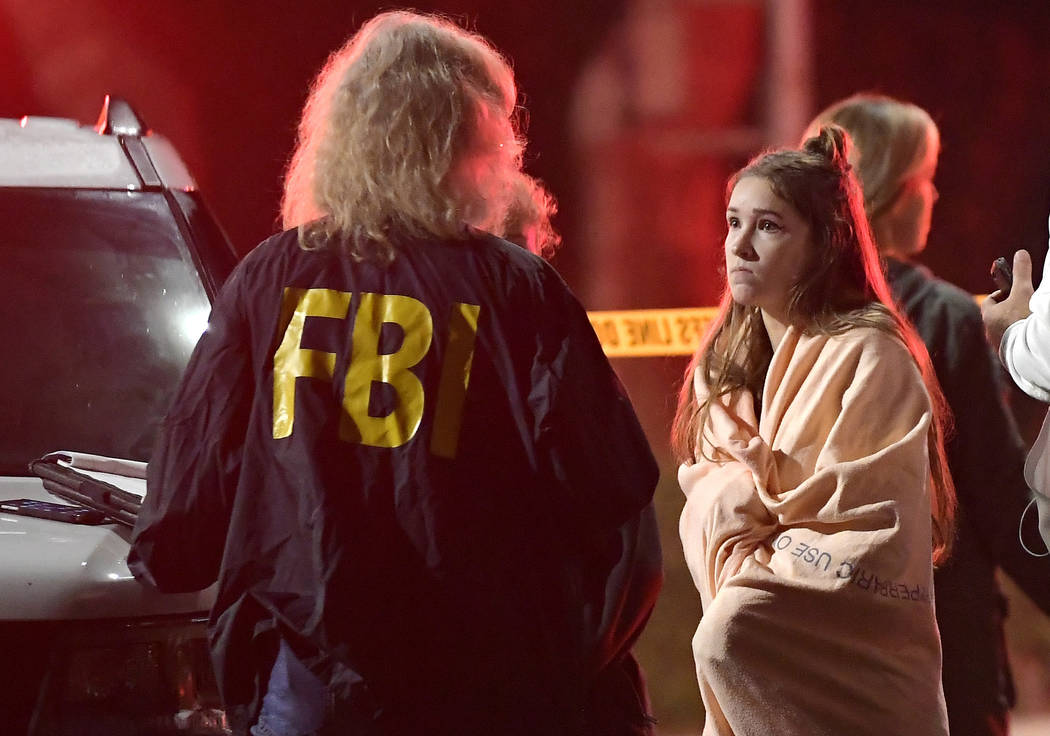 An FBI agent talks to a potential witness as they stand near the scene Thursday, Nov. 8, 2018, in Thousand Oaks, Calif. where a gunman opened fire Wednesday inside a country dance bar crowded with ...