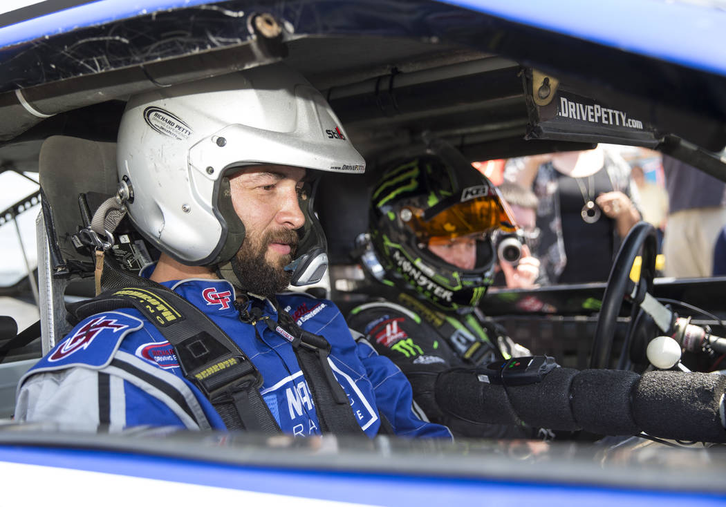 Vegas Golden Knights defenseman Deryk Engelland, left, prepares to take a ride in a race car with NASCAR driver Kurt Busch during a media event on Monday, Aug. 13, 2018, at the Las Vegas Motor Spe ...