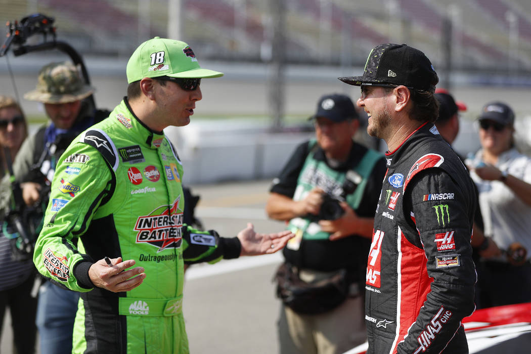 Kyle Busch, left, talks with his brother Kurt Busch before qualifications for a NASCAR Cup Series auto race at Michigan International Speedway in Brooklyn, Mich., Friday, Aug. 10, 2018. (AP Photo/ ...