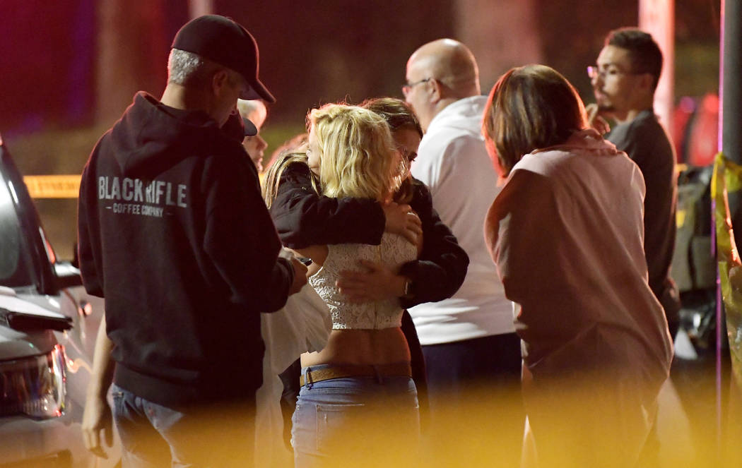 People comfort each other as they stand near the scene Thursday, Nov. 8, 2018, in Thousand Oaks, Calif., where a gunman opened fire Wednesday inside a country dance bar crowded with hundreds of pe ...