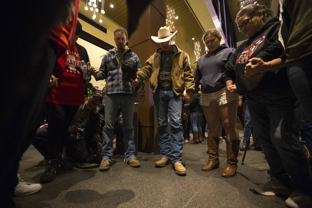 People hold hands in prayer for the victims of the Borderline Bar and Grill mass shooting during a candlelight vigil in Thousand Oaks, Calif., on Thursday, Nov. 8, 2018. Richard Brian Las Vegas Re ...