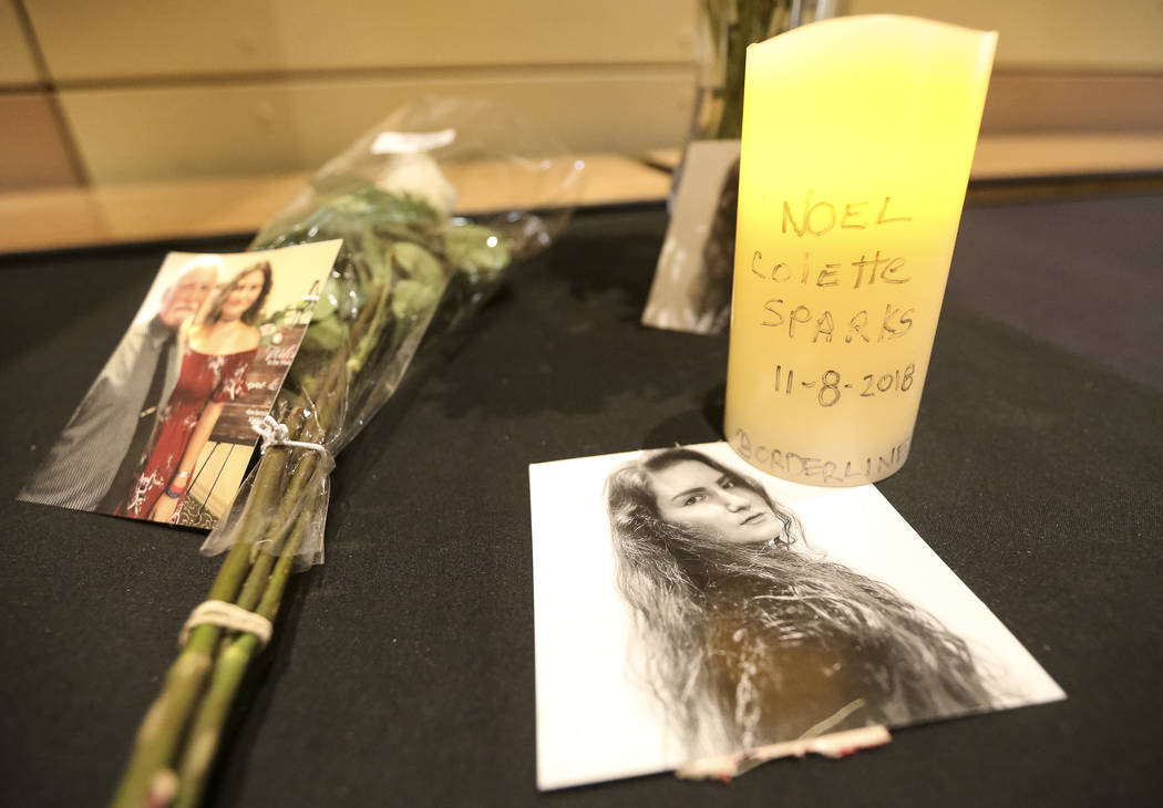 Photos remembering shooting victim Noel Colette Sparks sit among a bouquet of flowers and a burning candle during a candlelight vigil for victims of the Borderline Bar and Grill mass shooting in T ...