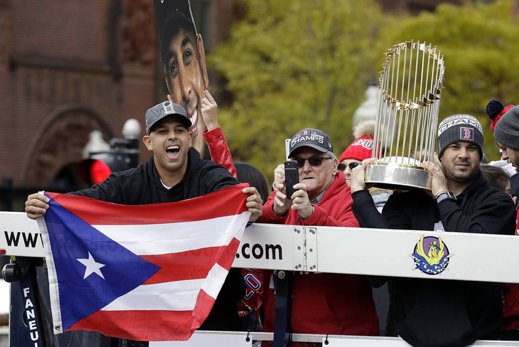 Boston Red Sox manager Alex Cora, left, waves the flag of Puerto Rico as coach Ramon Vazquez holds the championship trophy during a parade to celebrate the team's World Series championship over th ...