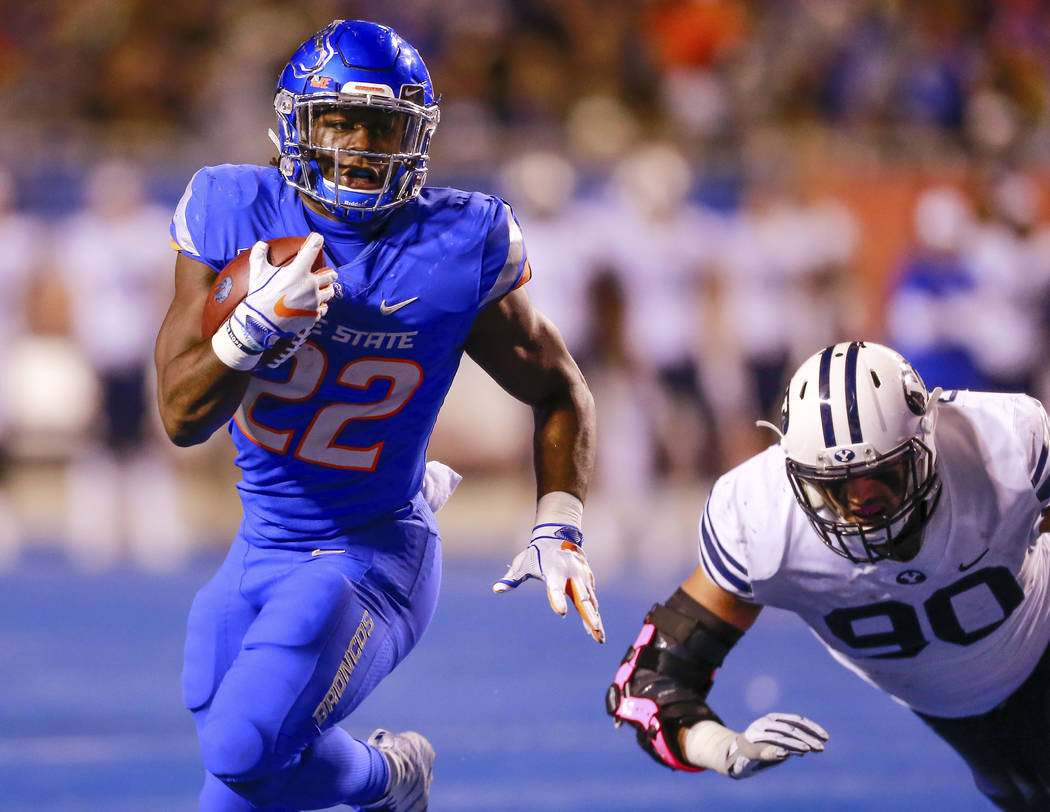 Boise State running back Alexander Mattison (22) runs past the diving BYU defensive lineman Corbin Kaufusi (90) in the second half of an NCAA college football game, Saturday, Nov. 3, 2018, in Bois ...