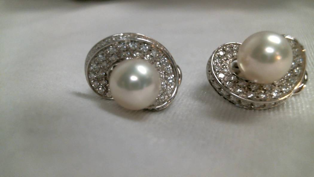 Pair of 18k white gold earrings with each earring peg set with one 8.8mm round cultured pearl, also pave set with 50 round brilliant diamonds. Appraised value $1,900.