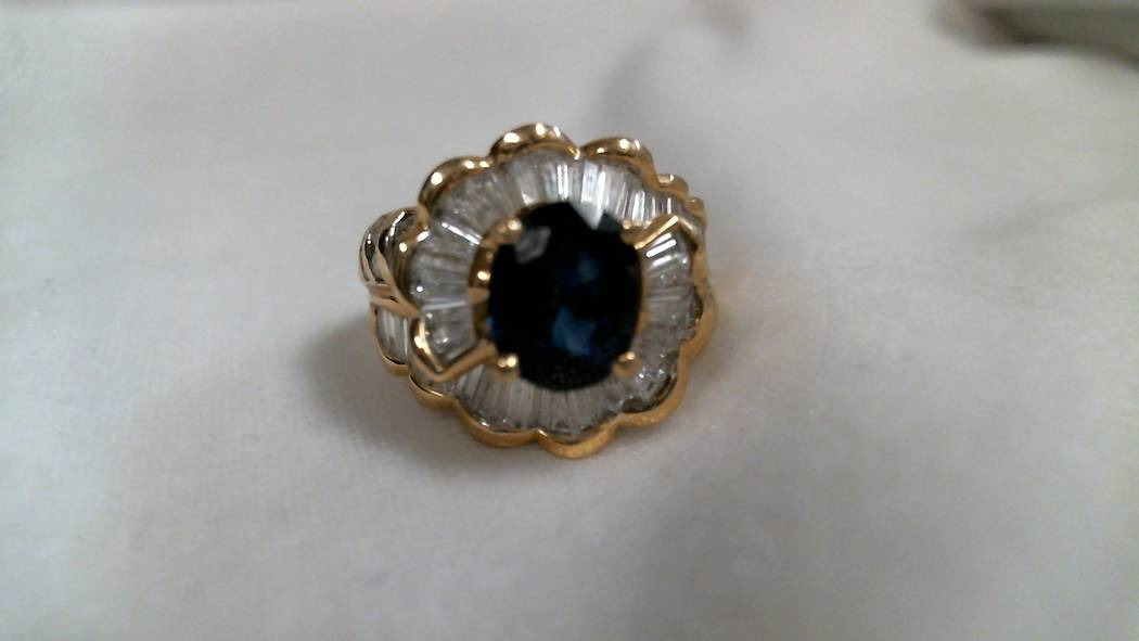 14k yellow gold spiral style ring centered with one 8.7x7.1x4.4mm oval dark blue sapphire surrounded by 49 baguette and 16 round brilliant diamonds. Appraised value $1,500.