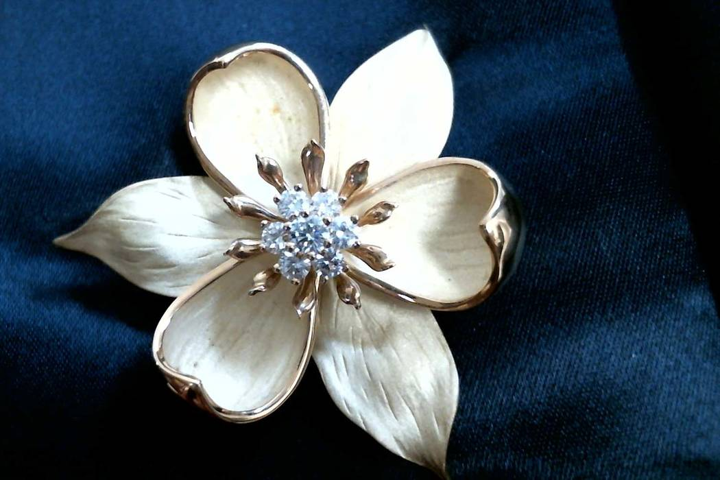 18k yellow gold Tiffany flower pin designed with five petals and centered with six .02 carat round brilliant diamonds and measuring 46 x 43 mm with a hinged pin and clasp on the back, total weight ...