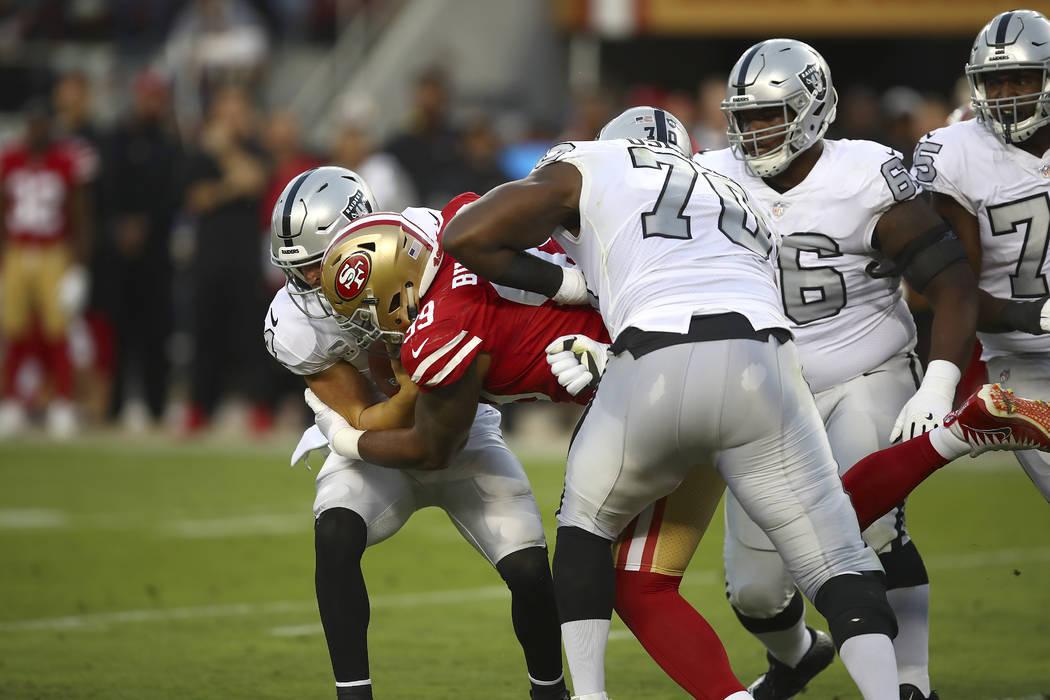 San Francisco 49ers defensive end DeForest Buckner, right, sacks Oakland Raiders quarterback Derek Carr during the first half of an NFL football game in Santa Clara, Calif., Thursday, Nov. 1, 2018 ...
