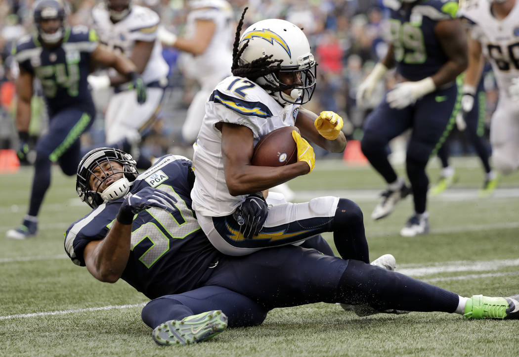 Seattle Seahawks' K.J. Wright (50) tackles Los Angeles Chargers' Travis Benjamin during the second half of an NFL football game, Sunday, Nov. 4, 2018, in Seattle. (AP Photo/Ted S. Warren)
