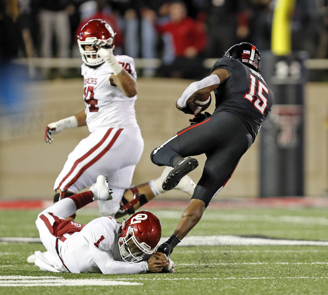 Texas Tech's Vaughnte Dorsey (15) breaks a tackle by Kyler Murray (1) after intercepting his pass during the first half of an NCAA college football game Saturday, Nov. 3, 2018, in Lubbock, Texas. ...