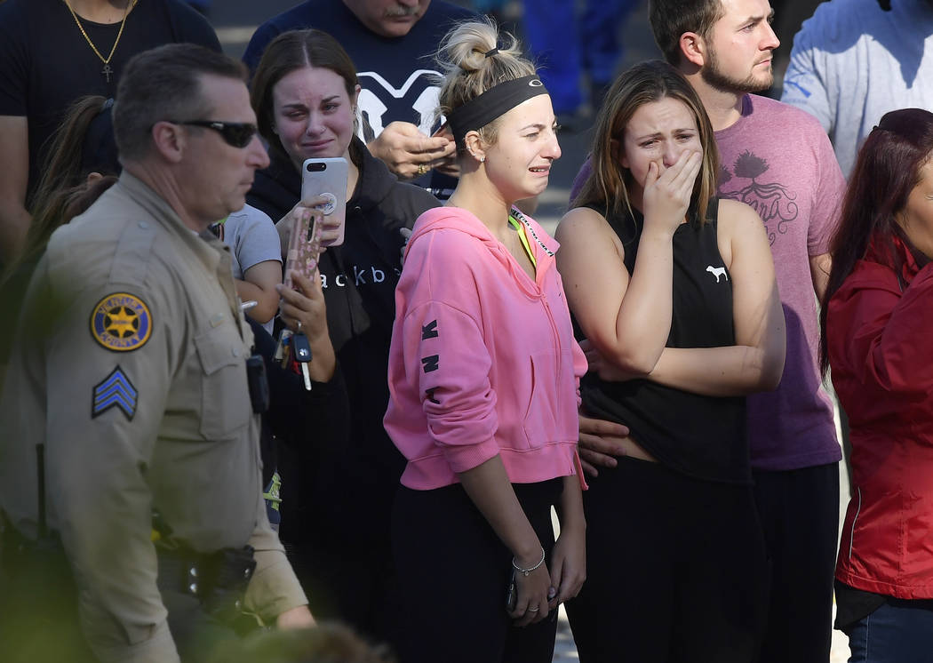 People cry as a law enforcement motorcade escorts the body of Ventura County Sheriff's Department Sgt. Ron Helus from the Los Robles Regional Medical Center Thursday, Nov. 8, 2018, in Thousand Oak ...