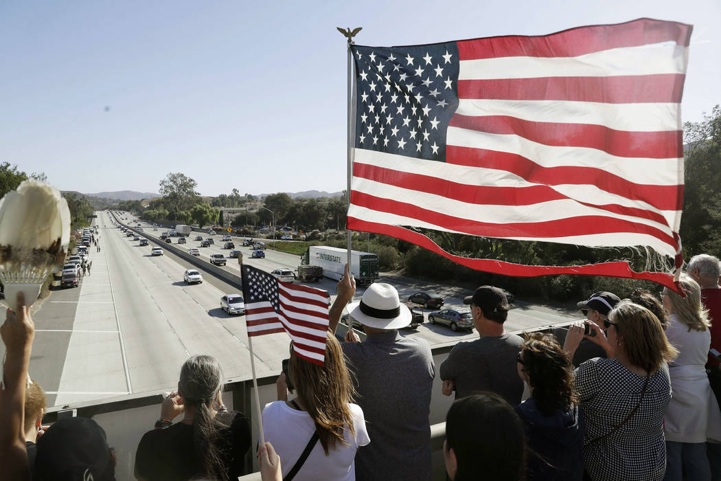 People look on from an overpass as a motorcade with the body of Ventura County Sheriff's Sgt. Ron Helus passes by Thursday, Nov. 8, 2018, in Newbury Park, Calif. Helus was fatally shot while respo ...