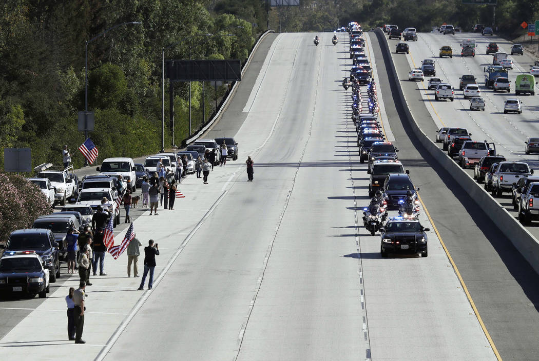 A law enforcement motorcade, providing an escort for a hearse carrying the body of Ventura County Sheriff's Sgt. Ron Helus, makes its way northbound on Highway 101 Thursday, Nov. 8, 2018, in Newbu ...