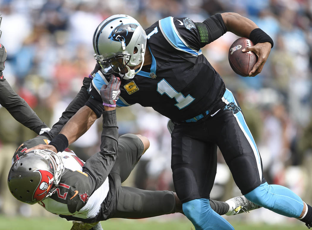 Tampa Bay Buccaneers' Justin Evans (21) grabs the face mask of Carolina Panthers' Cam Newton (1) in the first half of an NFL football game in Charlotte, N.C., Sunday, Nov. 4, 2018. (AP Photo/Mike ...