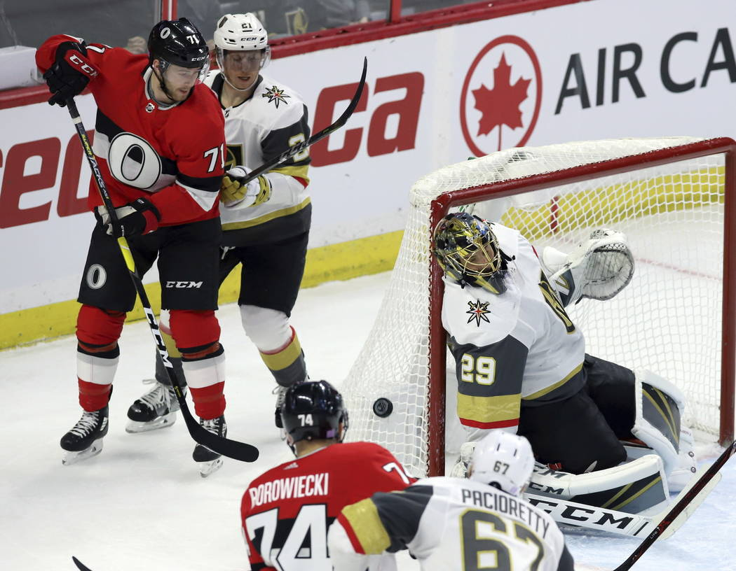 Ottawa Senators center Chris Tierney (71) and Vegas Golden Knights center Cody Eakin (21) look on as Vegas Golden Knights goaltender Marc-Andre Fleury (29) covers the side of the net during the fi ...
