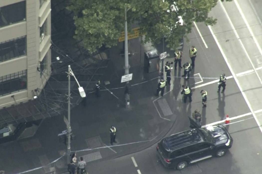 This image made from video shows police on street corner after a shooting in Melbourne, Australia, Friday, Nov. 9, 2018. Police shot a knife-wielding man Friday after he fatally stabbed one person ...