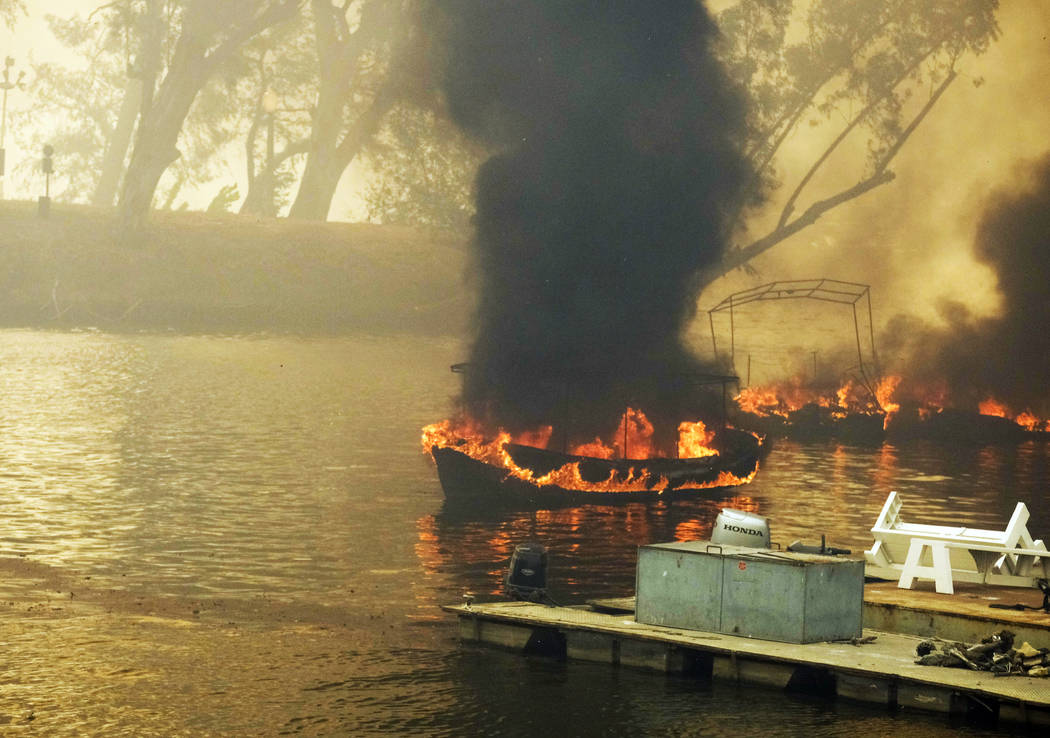 A wildfire burns boats on Malibu Lake in Malibu, Calif., Friday, Nov. 9, 2018. About two-thirds of the city of Malibu was ordered evacuated early Friday as a ferocious wildfire roared toward the ...
