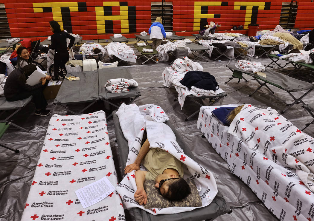 Evacuees from a wildfire rest on cots and blankets supplied by the Red Cross in the gymnasium at Taft Charter High School in the Woodland Hills section of Los Angeles on Friday, Nov. 9, 2018. (AP ...