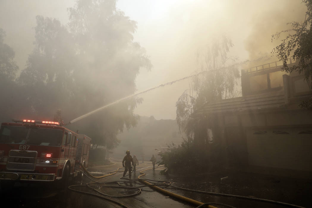 Firefighters spray water on a burning home Friday, Nov. 9, 2018, in Westlake Village, Calif. (AP Photo/Marcio Jose Sanchez)
