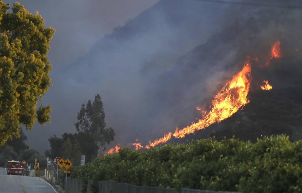 A wildfire comes down from a hilltop Thursday, Nov. 8, 2018, near Newbury Park, Calif. The Ventura County Fire Department has ordered evacuation of some communities in the path of the fire, which ...