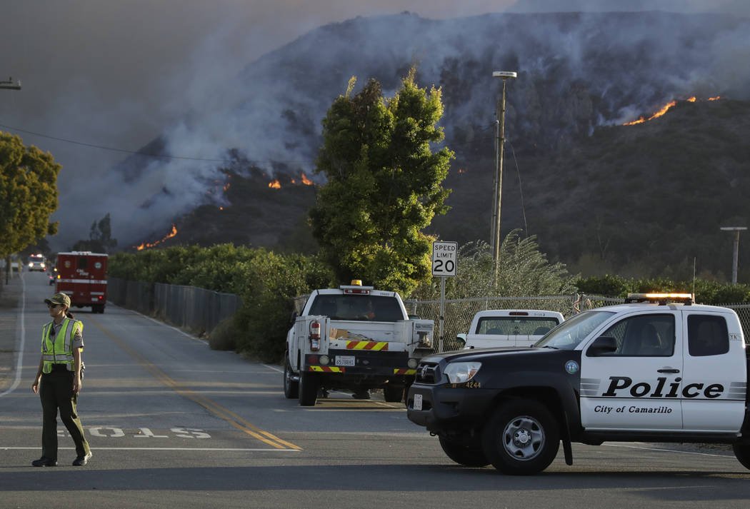 A police officer mans a checkpoint in front of an advancing wildfire Thursday, Nov. 8, 2018, near Newbury Park, Calif. The Ventura County Fire Department has ordered evacuation of some communities ...