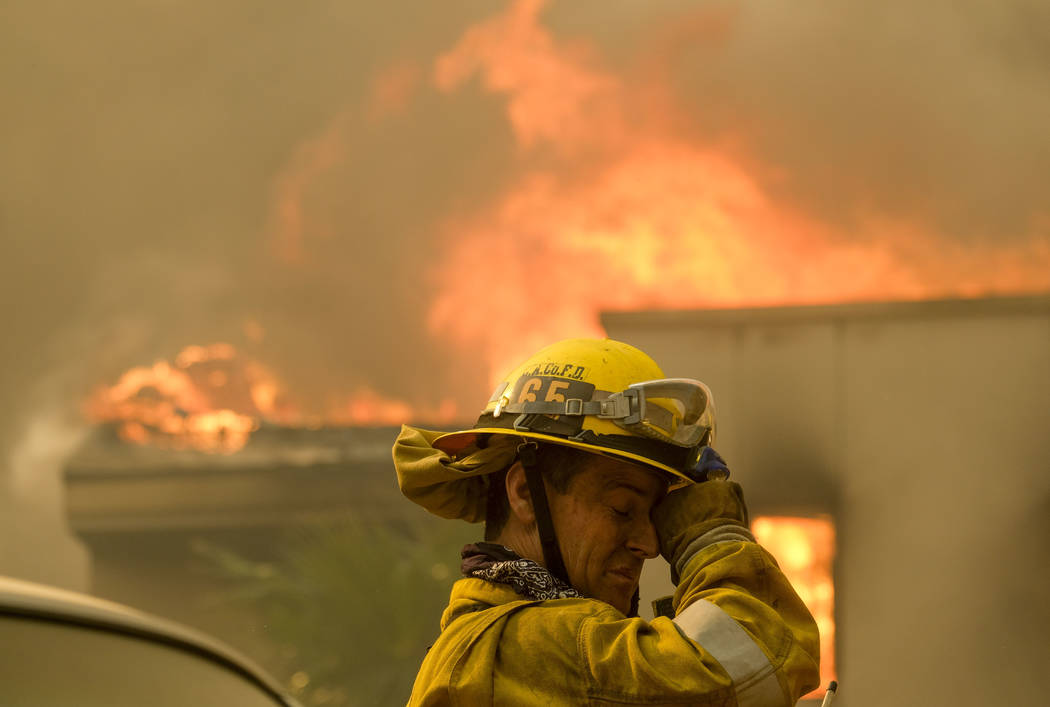 A firefighter keeps watch as the wildfire burns a home near Malibu Lake in Malibu, Calif., Friday, Nov. 9, 2018. About two-thirds of the city of Malibu was ordered evacuated early Friday as a fe ...