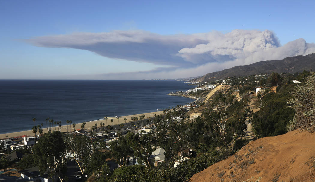 Strong winds blow smoke horizontally over the the Santa Monica Mountains and the Pacific Ocean over the city of Malibu, far distance, in Southern California, seen from the Pacific Palisades area o ...
