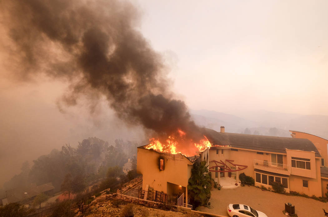 A wildfire burns a home near Malibu Lake in Malibu, Calif., Friday, Nov. 9, 2018. About two-thirds of the city of Malibu was ordered evacuated early Friday as a ferocious wildfire roared toward t ...