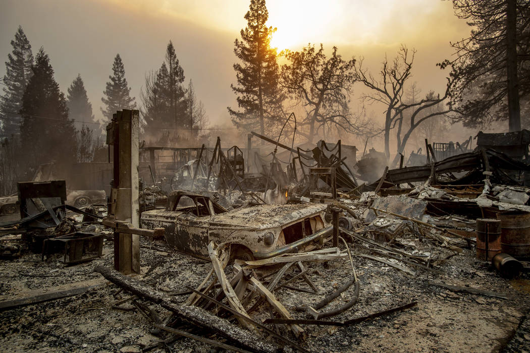 A vintage car rests among debris as the Camp Fire tears through Paradise, Calif., on Thursday, Nov. 8, 2018. Tens of thousands of people fled a fast-moving wildfire Thursday in Northern California ...