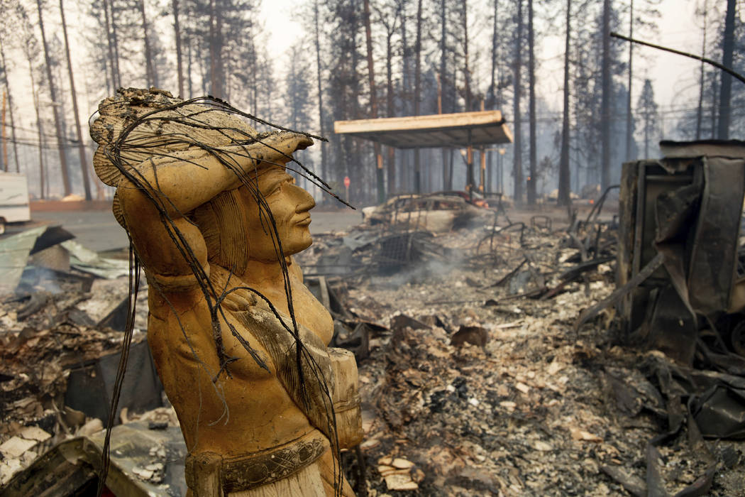 A statue rests amid a charred lot as the Camp Fire tears through Paradise, Calif., on Thursday, Nov. 8, 2018. Tens of thousands of people fled a fast-moving wildfire Thursday in Northern Californi ...