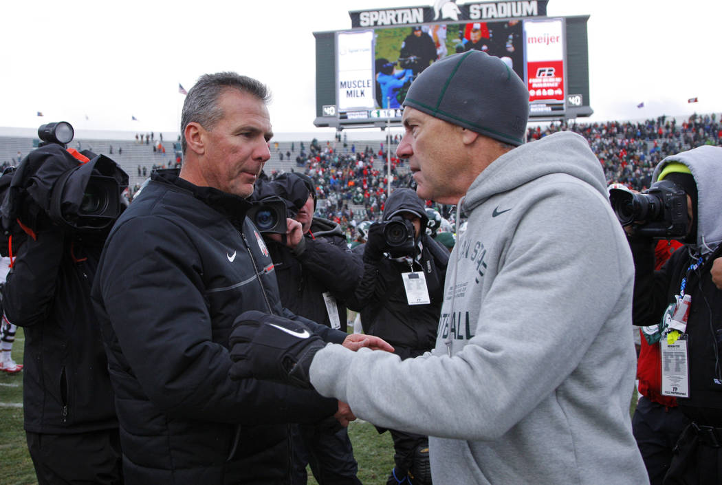 FILE - In this Nov. 19, 2016, file photo, Ohio State coach Urban Meyer, left, and Michigan State coach Mark Dantonio shake hands after the Spartans won 17-16 in NCAA college football game in East ...
