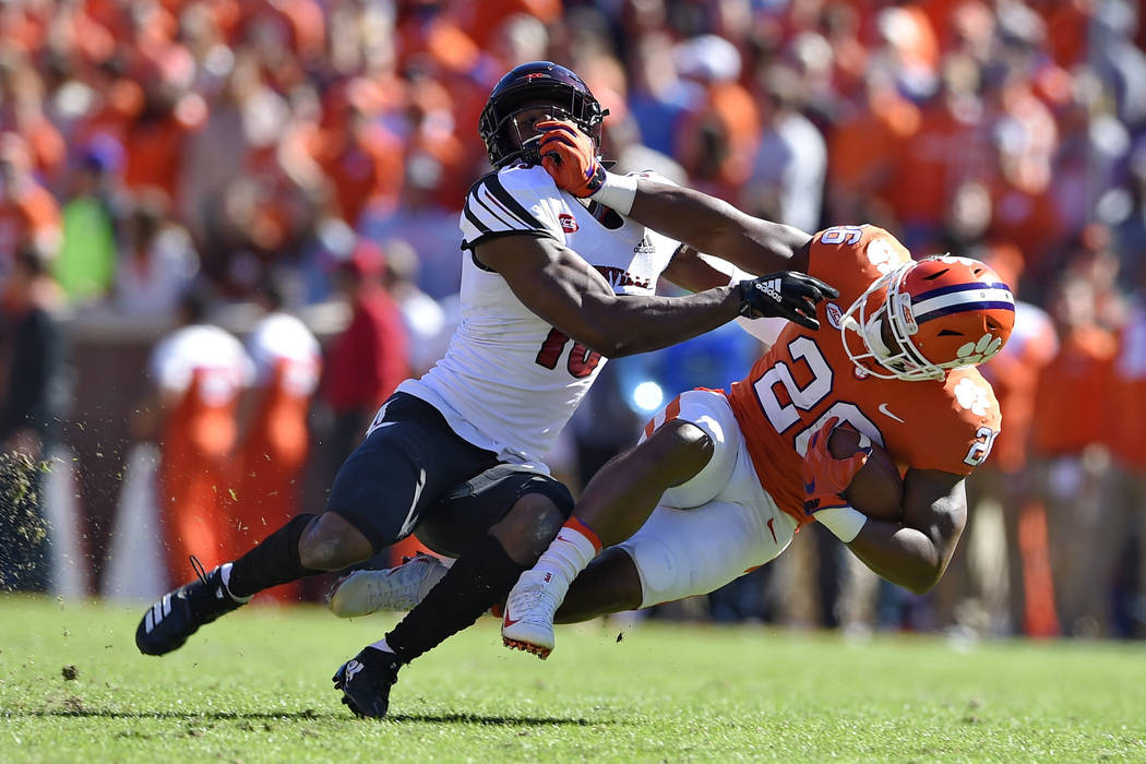 Clemson's Adam Choice (26) is brought down by Louisville's P.J. Blue during the first half of an NCAA college football game Saturday, Nov. 3, 2018, in Clemson, S.C. (AP Photo/Richard Shiro)