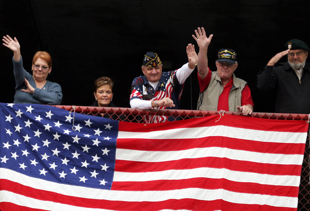 Parade goers, from left, Jeannine Holland, Jordy Wolf, Nick Wolf, John Holland and Pieter Krommenhoek wave or salute veterans as the march by during the 2006 Las Vegas Veterans Day Parade. The men ...