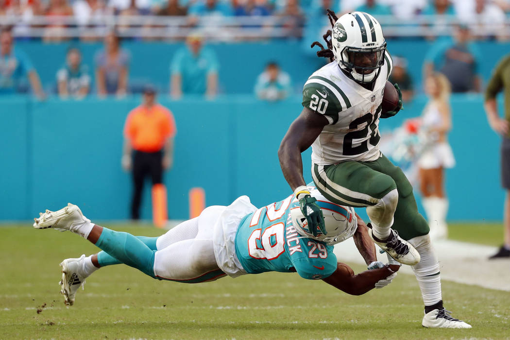 New York Jets running back Isaiah Crowell (20) avoids a tackle by Miami Dolphins free safety Minkah Fitzpatrick (29), during the second half of an NFL football game, Sunday, Nov. 4, 2018, in Miami ...