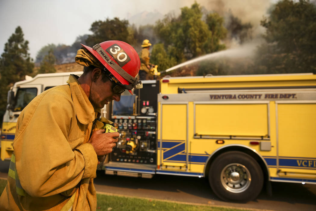 A Ventura County firefighter makes a call over his radio as members of his unit work to contain a wildfire along Lindero Canyon Road in Westlake Village, Calif., on Friday, Nov. 9, 2018. Richard B ...